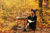 Young witch writing spells in forest
