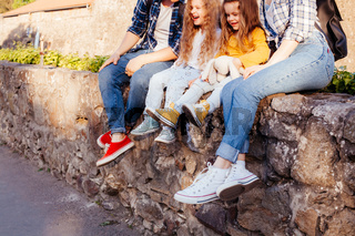The young family of four people sits outdoors