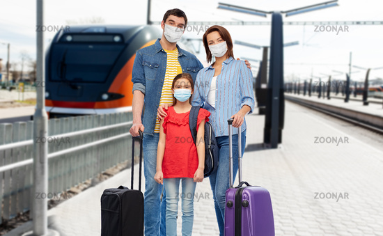 family in masks with travel bags over train