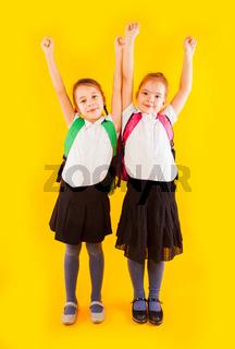 Two friendly schoolgirls in uniform holding hands up