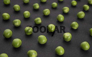Pattern of green peas on black background