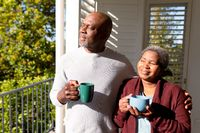 Relaxed african american senior couple drinking coffee standing on balcony in sun