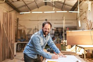 Start-Up Gründer mit Bauzeichnung in Tischlerei