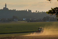 Typical Bavarian rural farm labor scene with tractor plowing field and pilgrimage church on top of hill in background in evening sunlight