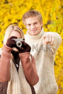 Autumn couple take photo camera in park