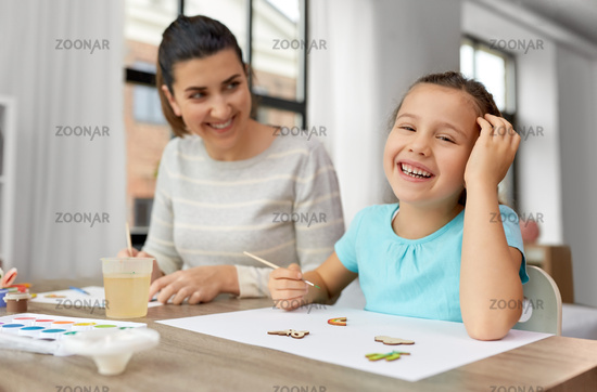 happy mother with little daughter drawing at home
