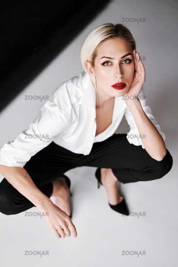 Top view portrait of daring trendy woman posing on white studio background sitting on floor