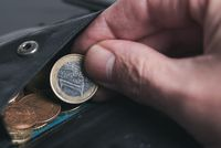 close-up of person picking 1 Euro coin from wallet