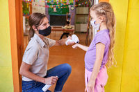 Kindergärtnerin beim kontaktlos Fieber messen