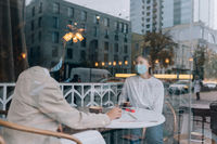 Friends girls met in a cafe. Wear medical protective masks.