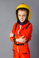 The little boy is posing in a parachute costume