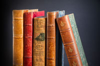 Row of old books on dark background