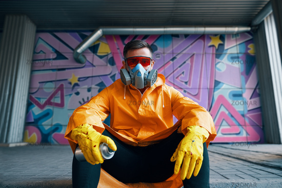 Graffiti painter rest near the wall with his paintings looking to camera