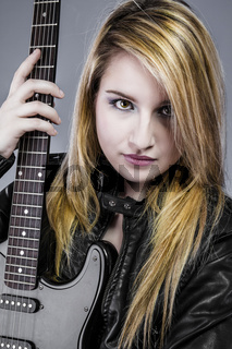 Sexy young blonde dressed in black leather holding black electric guitar