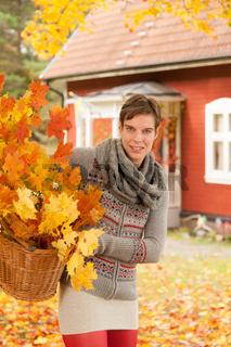 Junge attraktive Frau sammelt Herbstlaub