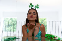 Caucasian woman celebrating st patrick's day making video call wearing deely boppers blowing kiss