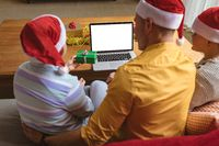 Caucasian father and two sons showing christmas gifts during video call on laptop with copy space