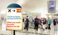 a signal inside an airport that warns about what to know before flying to England during the Covid-19 pandemic
