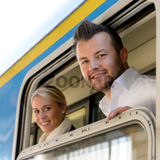 Man and woman in train looking window