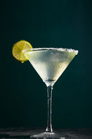 Glass of martini with cocktail or mocktail and lime wedge on dark background