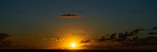 Sonnenuntergang als Panorama Hintergrund mit Wolken