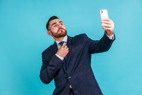 Portrait of self-confident man with beard wearing official style suit straighten a tie and making selfie or broadcasting livestream.