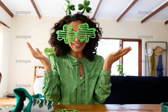 Caucasian woman dressed in green with shamrock glasses making st patrick's day video call