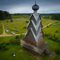 wooden church in the summer on the edge of the forest.