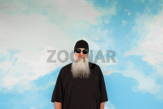 Portrait of mature man with long gray beard against blue sky and cloud background wall outdoors wearing sunglasses