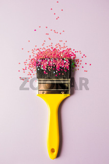 Scattering pink small hearts on the brush