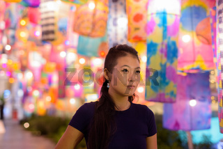Portrait of beautiful Asian woman thinking with traditional colorful lantern lights outdoors at night