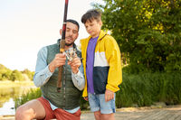 happy father and son fishing on river
