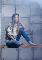 Portrait of young beautiful blonde woman is sitting on a board on smoke and metal wall background.