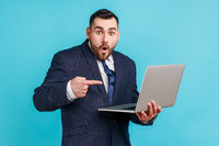 Portrait of shocked bearded man wearing official style suit holding laptop and pointing at screen, surprised about computer application, internet news.