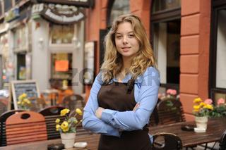 Portrait einer Kellnerin vor dem Restaurant