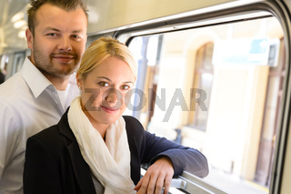 Woman and man standing by train window