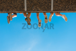 Boys legs in shoes hanging from the bridge against blue sky