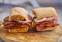 Thin cut pastrami sandwhich with delicious meet on baguette bread with chedder cheese, onion