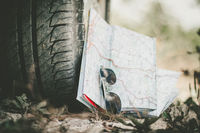 Adventure trip: close of car tyre, sunglasses and road map