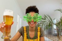 Mixed race woman celebrating st patrick's day making video call holding a beer