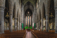 Rows of benches, tall columns, stained glass and main altar in St. Marys Cathedral