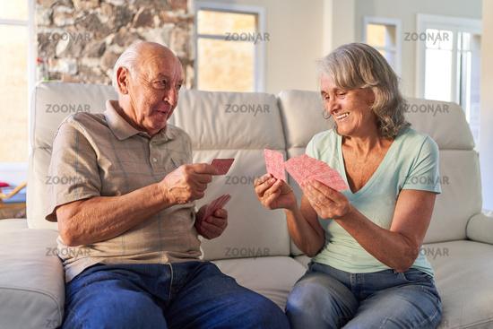 Senioren Paar im Ruhestand beim Karten spielen auf dem Sofa