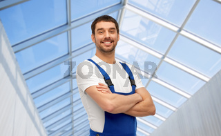 happy smiling male worker or builder in glasshouse