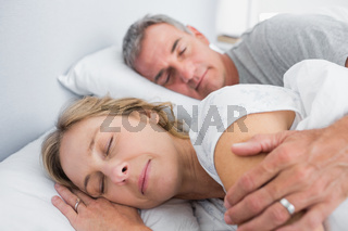 Calm couple sleeping and spooning in bed