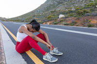 Fit african american woman in sportswear sitting and resting on a coastal road