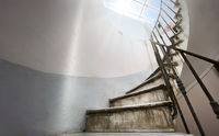 Ancient spiral staircase with marble steps and wrought iron handrail.