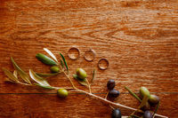 Gold wedding rings and an engagement ring on a brown background with a sprig of olive tree fruits.