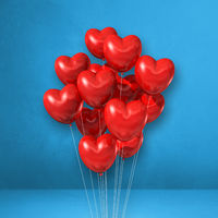 Red heart shape balloons bunch on a blue wall background