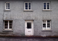 an old abandoned grey derelict house on a residential street with dirty broken windows
