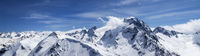 Panorama of high snow-capped mountain peaks and beautiful blue sky with clouds